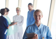 Female doctor with tablet computer  standing in front of team. In background, group of medical staff at hospital Stock Photos