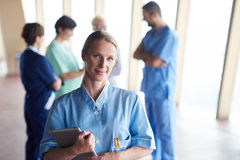 Female doctor with tablet computer  standing in front of team Royalty Free Stock Photo