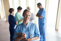 Female doctor with tablet computer  standing in front of team. In background, group of medical staff at hospital Royalty Free Stock Images