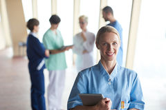 Female doctor with tablet computer  standing in front of team. In background, group of medical staff at hospital Royalty Free Stock Photo