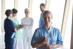Female doctor with tablet computer  standing in front of team Stock Photo