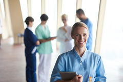 Female doctor with tablet computer  standing in front of team Stock Photography