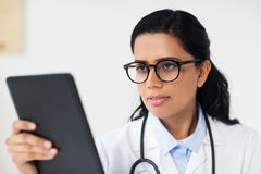 Female doctor with tablet pc at hospital. Healthcare, technology, people and medicine concept - female doctor in glasses with tablet pc computer at hospital Stock Images