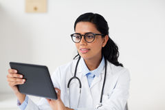 Female doctor with tablet pc at hospital. Healthcare, technology, people and medicine concept - female doctor in glasses with tablet pc computer in medical Stock Photography