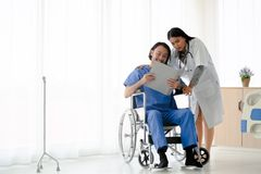 Female doctor take care of male patient who sitting on wheelchair. Female doctor take care of smiling asian male patient who sitting on wheelchair with document stock photos