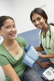 Female Doctor Taking Girl's Blood Pressure. Happy female doctor taking teenage girl's blood pressure in the clinic stock photo