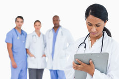 Female doctor taking notes on clipboard with staff members behin Stock Photos