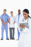 Female doctor taking notes with staff members behind her Stock Image