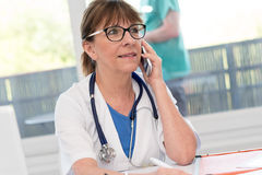 Female doctor talking on mobile phone Royalty Free Stock Images