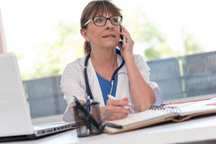 Female doctor talking on mobile phone Stock Photos