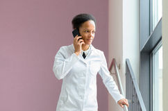 Female doctor talking on a mobile phone. Serious young female doctor talking on a mobile phone while she listens to the conversation standing in a hospital Royalty Free Stock Photos