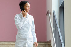 Female doctor talking on a mobile phone. Serious young female doctor talking on a mobile phone while she listens to the conversation standing in a hospital Royalty Free Stock Images