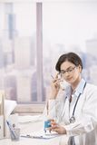 Female doctor talking on phone Royalty Free Stock Photography