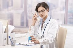 Female doctor talking on phone Stock Photography