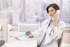 Female doctor talking on phone Royalty Free Stock Photo