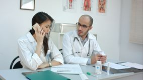 Female doctor talking on the phone asking her male coworker for advice royalty free stock photos