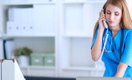 Female doctor talking on phone in diagnostic center Stock Image