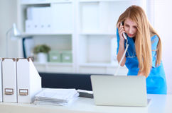 Female doctor talking on phone in diagnostic center Royalty Free Stock Photos