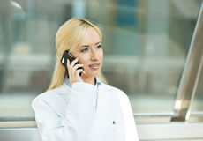 Female doctor talking on a phone with patient Stock Image