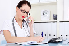 Female doctor talking by the phone and writing. Attractive female doctor talking by the phone and writing Stock Image