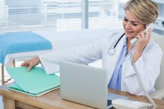 Female doctor talking on telephone. In clinic Royalty Free Stock Photos