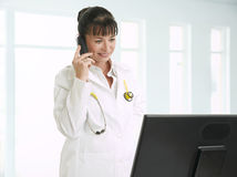 Female doctor talking on telephone Royalty Free Stock Photography