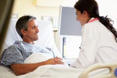Female Doctor Talking To Male Patient In Hospital Room stock photography