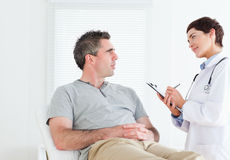 Female doctor talking to a patient. In a room Royalty Free Stock Photos