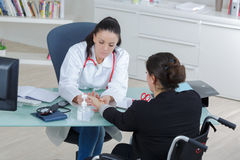 Female doctor talking to patient on wheelchair Royalty Free Stock Photos