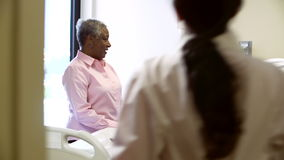Female Doctor Talking To Senior Couple In Hospital Room stock video footage