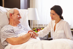 Female Doctor Talking To Senior Male Patient In Hospital Bed Royalty Free Stock Image