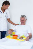 Female doctor talking to senior man while having breakfast Royalty Free Stock Photo