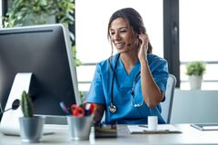 Free Female Doctor Talking With Earphone While Explaining Medical Treatment To Patient Through A Video Call With Computer In The Stock Images - 217076734