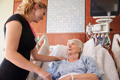 Female Doctor Talks To Senior Female Patient In Hospital Bed Stock Images