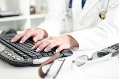 Female doctor taping on a computer keyboard Stock Photos