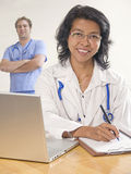 Female Doctor team. Smiling and confident female Asian Doctor sitting down and writing with caucasian Doctor in background Royalty Free Stock Photo