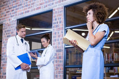 Female doctor thinking while checking a file near library. Female doctor checking a file near library and colleagues standing behind Royalty Free Stock Photography