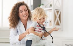 Female doctor tickling little boy in office. Copy space royalty free stock photo