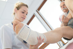 Female doctor touch foot patient. Female doctor touch the foot of patient Royalty Free Stock Image