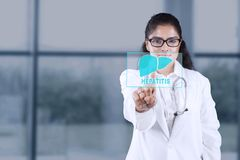 Female doctor touching a liver symbol. Picture of female doctor standing in the hospital while touching a virtual button with liver symbol Stock Photography