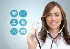 Female doctor touching stethoscope on digitally generated medical icons against white background Royalty Free Stock Photos