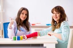 Female doctor traumatologist bandaging female patient. The female doctor traumatologist bandaging female patient stock images