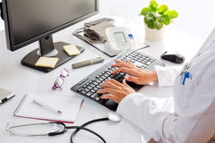 Female doctor. Female doctor typing on desktop computer, inside her office Stock Photography