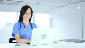 Female doctor typing on laptop in hospital. 4k, high quality stock footage