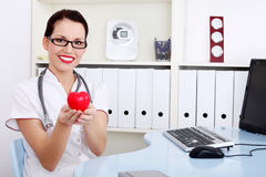 Female doctor in uniform holding heart. Royalty Free Stock Photos
