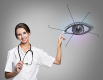 Female doctor in uniform touch painted human eye Royalty Free Stock Photography
