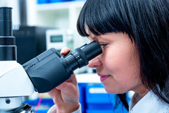 Female doctor uses microscope Stock Images