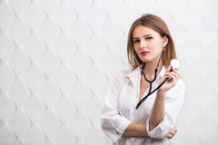 Female Doctor Uses Stethoscope. Female doctor holding stethoscope, wearing doctor`s smock, cheerful caucasian woman  before white background Royalty Free Stock Photos