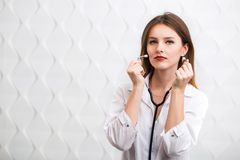 Female Doctor Uses Stethoscope. Female doctor holding stethoscope, wearing doctor`s smock, cheerful caucasian woman  before white background Royalty Free Stock Images