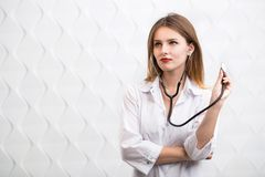 Female Doctor Uses Stethoscope. Female doctor holding stethoscope, wearing doctor`s smock, cheerful caucasian woman  before white background Royalty Free Stock Image